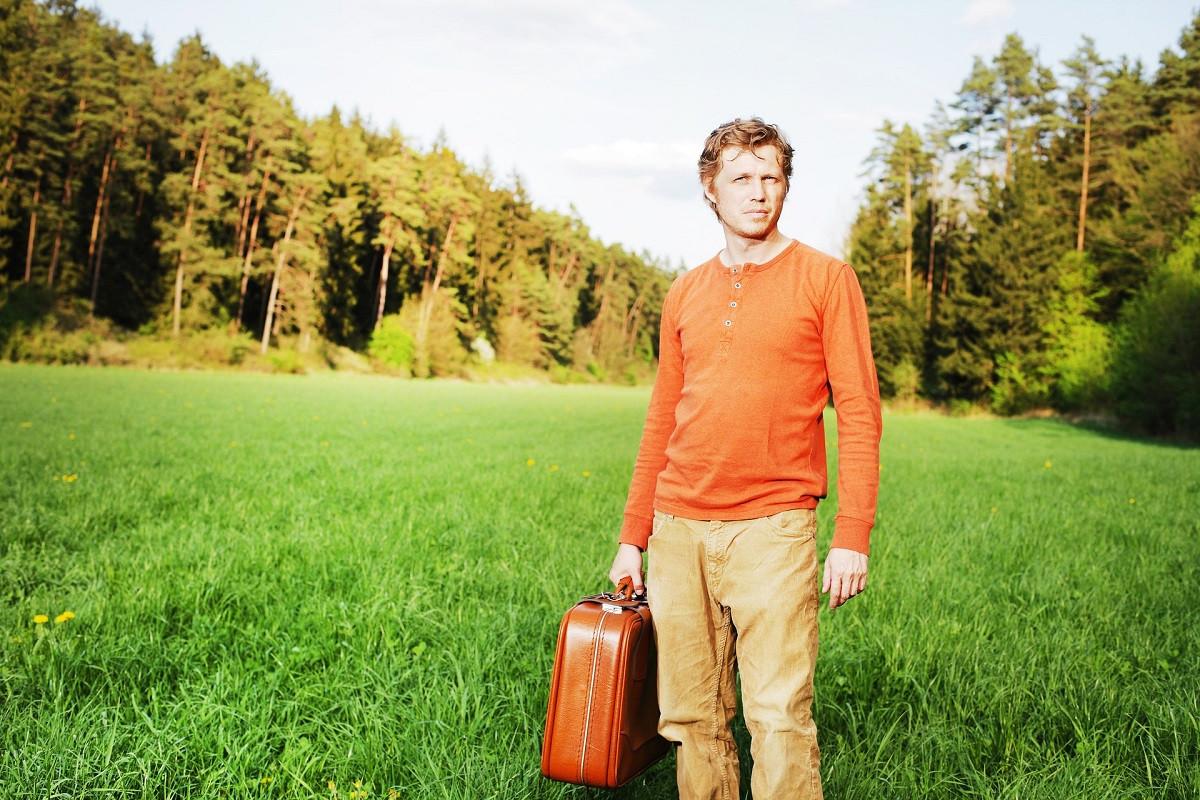 man met koffer natuur